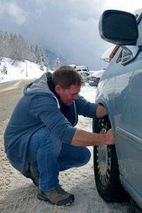 un homme en train de mettre une chaussette contre la neige
